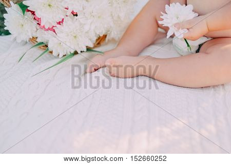 little baby on the bed legs and a bouquet of white flowers