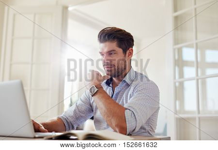 Young Man At Home Working On Laptop