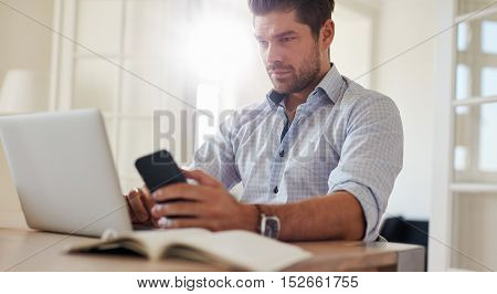 Man Sitting At Desk With Laptop And Mobile Phone At Home