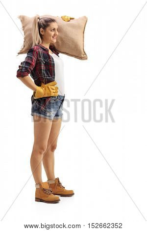 Full length profile shot a female agricultural worker holding a burlap sack isolated on white background