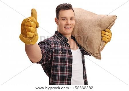 Joyful male farmer holding a burlap sack and giving a thumb up isolated on white background