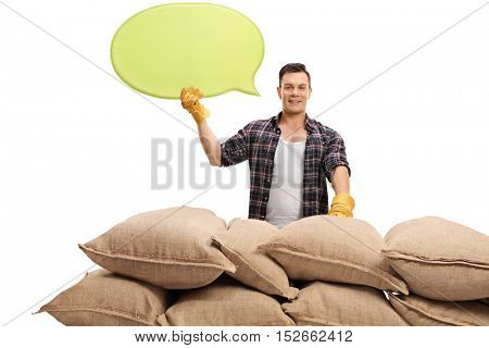Male agricultural worker posing behind a pile of burlap sacks with a speech bubble isolated on white background