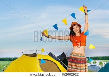 Portrait of beautiful smiling girl, holding garland with yellow and blue flags, standing next to the tent at hippie campsite