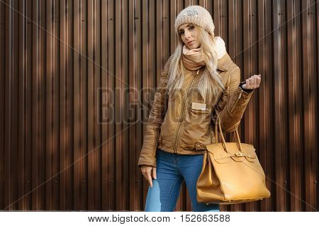Attractive girl in wool hat and leather jacket jeans with beige bag stands near the brown fence on the street in the hands of