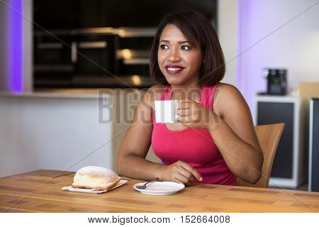 beautiful hispanic woman sitting at table with coffee and pastry looking happy