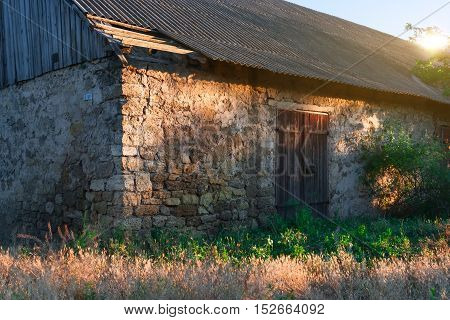 Closed wooden door in a stone wall of an old shed.