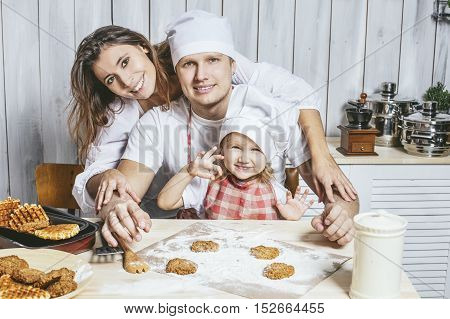 Family happy daughter with dad and mom in home kitchen laughing and preparing food together with love
