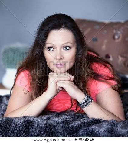 beautiful brunette lying on couch and looking thoughtfully