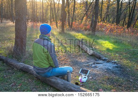 Man resting in autumn forest after the drone control sitting among the trees near remote controller of drone and thermos.
