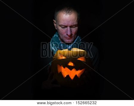 Man looks into the Jack lantern at the halloween night. Man and glowing pumpkin in the dark.