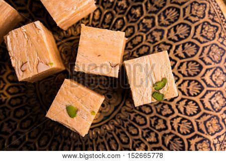 Close-up of soan papdi or son papdi with almonds and pistachio or pista