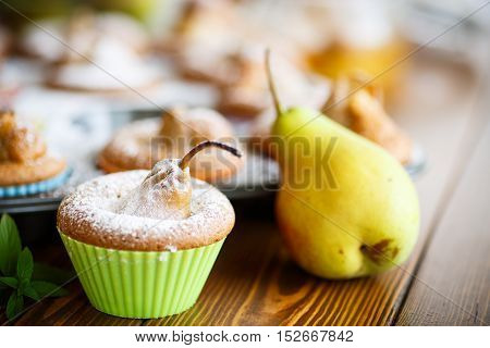 sweet muffins with pears in powdered sugar