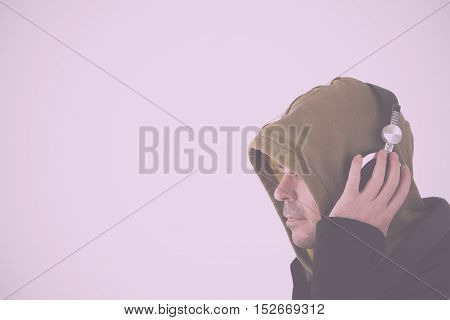 Man In Hoodie Listening To Headphones Vintage Retro Filter.
