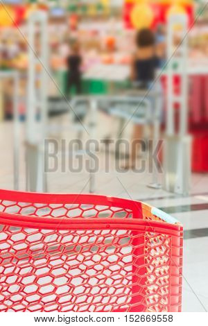 abstract supermarket red cart with shop blured background