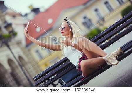 Pretty girl is taking selfie sitting on a bench