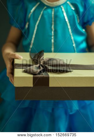 A small girl holding a golden gift box in hand. Close up shot from front angle.