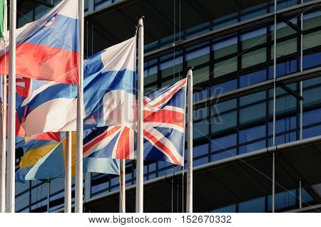 United Kingdom of Great Britain and Northern Ireland or Union Jack flag against front glass facade of European Parliament