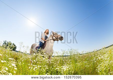 Portrait of pretty woman horseriding in the flowery meadow at sunny day