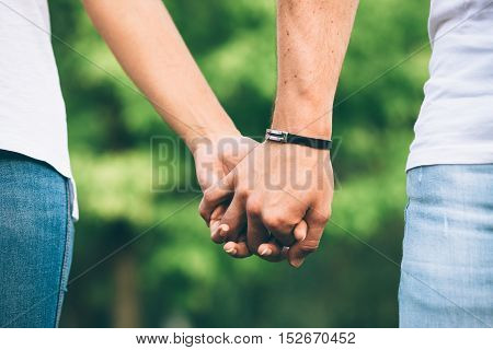 Detail of lovers clasped hands. Dating and love concept.
