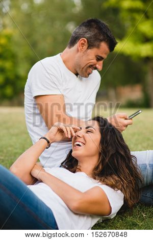 Loving young couple having fun and enjoying leisure on summer or spring at the park. Joyful man and woman dating outdoor.