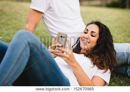 Young couple relaxing and enjoying tranquility outdoor. Cheerful woman texting on smartphone. Focus on the girl.