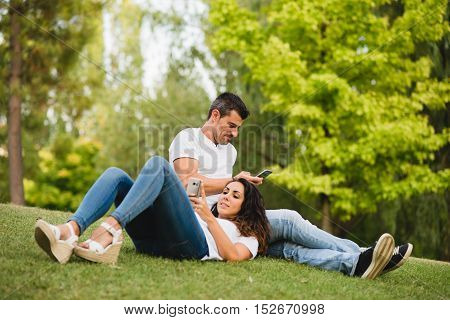 Young couple texting in the smartphone and relaxing together outdoor. Man and woman enjoying summer or spring leisure and tranquility.