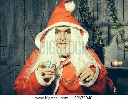 New year man with smiling face with long white beard and hair in red santa claus christmas coat holding clock medallion on chain