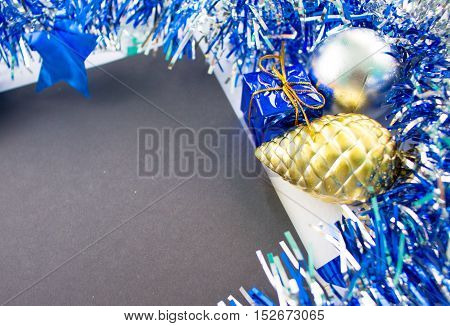 Christmas or New Year flat composition. Blue sparkling ribbon wreath. Fir pine toy and gift. Black paper with blank page. Season image for greeting card or advertisement. Festive closeup background