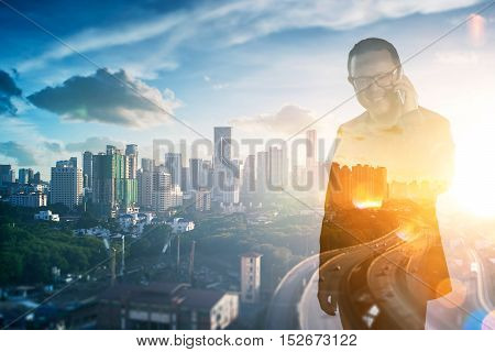 Double exposure photo a Smiling businessman in eyeglasses talking on the phone with view of the city