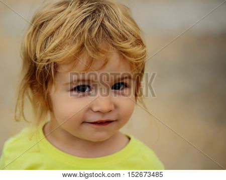 Cute baby boy child with curly blond curly hair in yellow shirt and brown eyes outdoor on blurred background close up