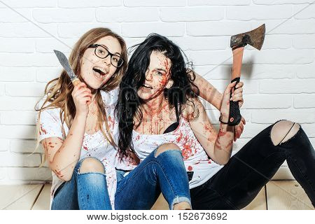 Two zombie girls young halloween women with brunette and blond bloody hair with wounds and red blood scare with knife and axe on brick wall