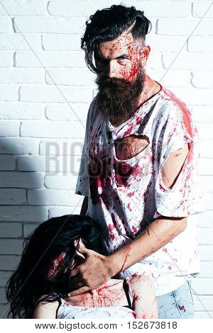 Bearded man zombie bloody hipster and creepy girl young woman with wounds and red blood on brick wall