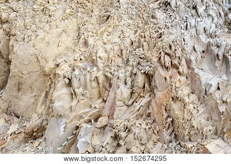 Beige rock or sharp stone formations minerals solid layer wall on sea coast beach on natural background