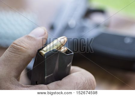 Load 9Mm Ammo In The Pistol Clip Close Up. Hands, Bullets, Magazine And Handgun.