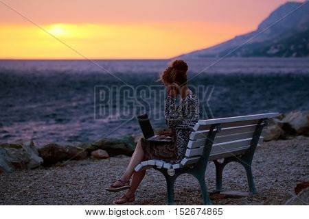Woman With Laptop On Evening Beach