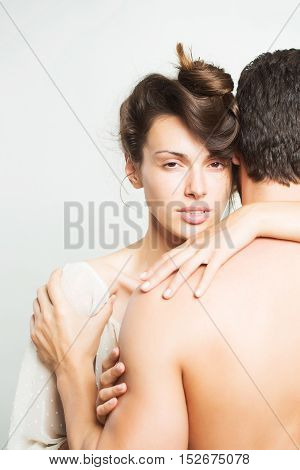 young sexy couple of muscular man embracing with back and pretty woman or girl with brunette hair in studio on grey background