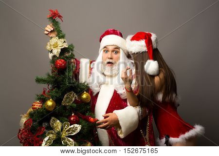 Amazed santa claus man with white beard and hair in new year red suit listens to whisper of pretty sexy girl
