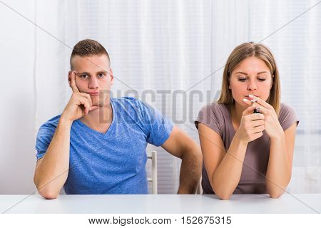 Husband is very sad because his wife doesn't want to stop smoking.