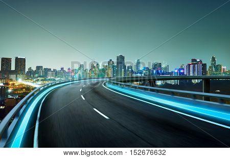 Blue neon light highway overpass motion blur with city skyline background night scene .