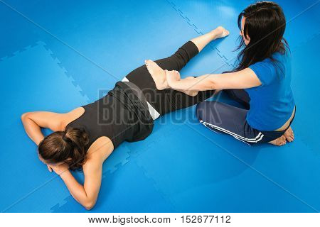 Physical therapist working with female athlete, toned image