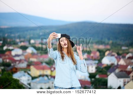 Young girl with pretty sexy cute face with fashion makeup in black baseball and blue shirt making selfie with smartphone and showing devil horns rock gesture on roofs houses and mountains background