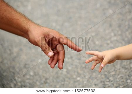 Little fragile baby hand reach to fathers finger on gray background