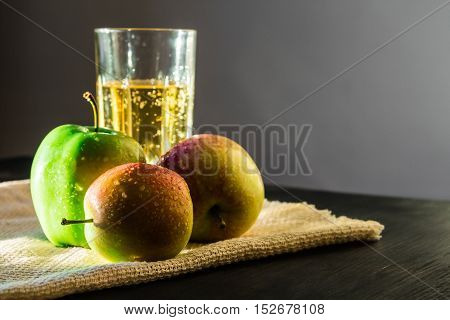 Apples and sparkling apple wine. Fresh apples and a glass of sparkling apple wine on canvas napkin in the natural sun light.