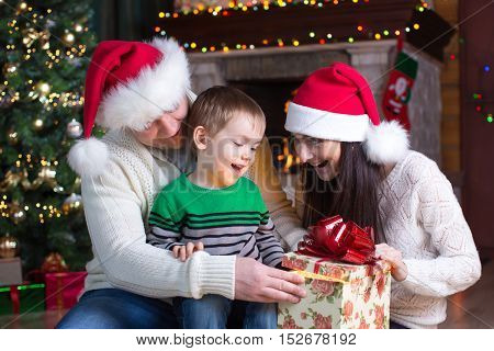 holidays presents christmas concept - happy mother father and kid boy with gift box