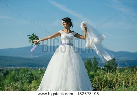 sexy bride cute happy woman with pretty face with flying wedding veil and white lace dress on sunny summer field on blue sky background