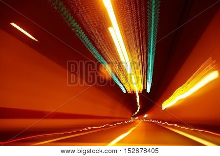 abstract blurred or defocused light motion on speed race in illuminated road tunnel yellow color as design flash background