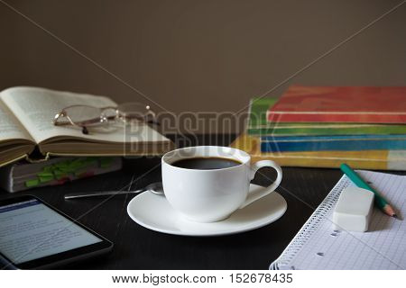 Coffee in front of textbooks,smartphone and notebook on a dark wood table. Black wood table with cup of coffee, textbooks, smartphone, reading glasses and notebook.