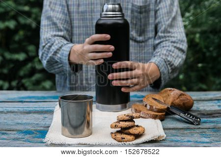 Thermos, cookies, metal cup, bread slices on wooden table. Metal cup with coffee, chocolate chip cookies, whole-wheat bread on vintage wood table and hands holding thermos on natural green background.