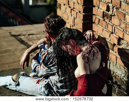 Bearded man zombie bloody hipster and creepy girl young woman with wounds and red blood halloween couple sit outdoors at brick wall