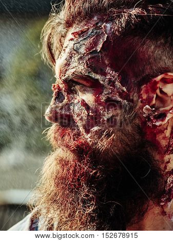 Bearded zombie man with beard halloween vampire or bloody war soldier with wounds and red blood outdoors on natural background